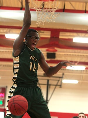 West High's Wali Parks dunks the ball during the Trojans' game at City High. Parks scored four points in the game as the Trojans downed their rivals to move to 8-0 on the year.