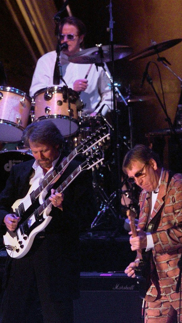 Eagles members Don Felder, left, Joe Walsh, right, and Don Henley, background, perform at the Rock and Roll Hall of Fame induction ceremony in New York Jan. 12, 1998. One of the hottest bands of the '70s, the Eagles were inducted into the Hall of Fame. (AP Photo/Kathy Willens)