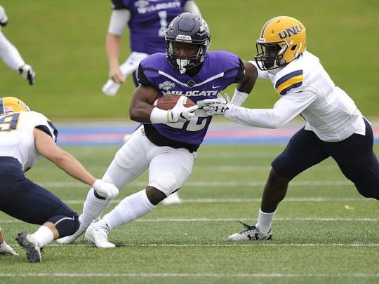 Thomas Metthe/Reporter-News Abilene Christian running back De'Andre Brown (22) runs between a pair of Northern Colorado defenders during the first quarter of the Wildcats' 55-52 loss on Saturday, Sept. 10, 2016, at Shotwell Stadium.