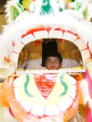 Haiden Small looks through the mouth of the Mountain Dragon School's lion costume January 24, 2017.