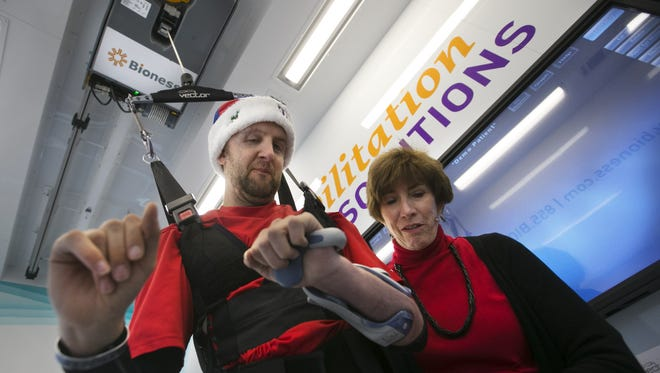 Cory Remsburg uses the Bioness Vector with the help of physical therapist Kay Wing. The veteran, injured in Afghanistan, hopes to raise funds so SWAN Rehab in Phoenix can buy the device.