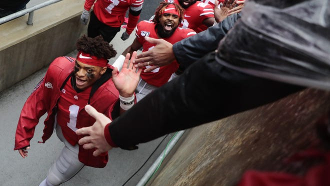 Ohio State quarterback Justin Fields, left greets fans as he heads to the locker room following a 38-7 victory over Wisconsin last October at Ohio Stadium. While a season restart will draw in television revenue, money from game days will be lost.