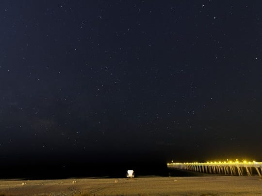 The Milky Way and Scorpius constellation rising over the Gulf and the fishing pier.