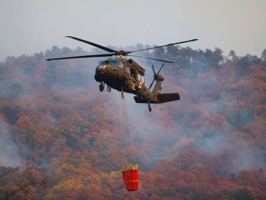 An Air National Guard helicopter prepares to retrieve water from the Little River before dropping it on a wildfire in Blount County near Walland Elementary School Friday, Nov. 18, 2016.