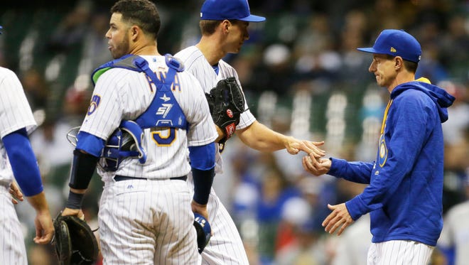 Brewers relief pitcher Brent Suter hands the ball to manager Craig Counsell during the game against the Chicago Cubs on April 7.