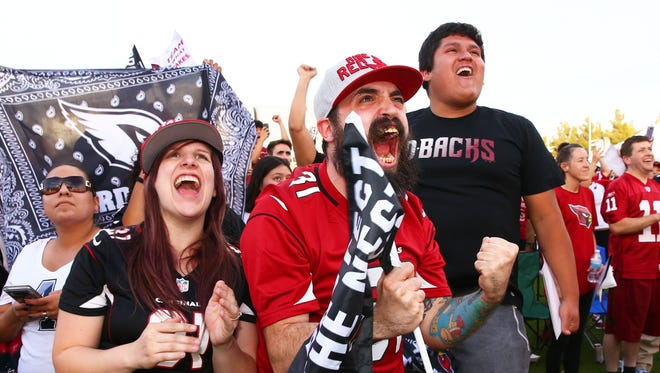 Fans Chelsea and Nicholas Westfall react as the Cardinals pick UCLA QB Josh Rosen at the Arizona Cardinals draft party on Apr. 26, 2018 on the Great Lawn outside University of Phoenix Stadium in Glendale, Ariz.