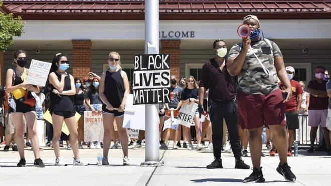 Xzavier Brandon, on the right uses a bullhorn to address a crowd Saturday during a protest he helped to organize in New Albany.