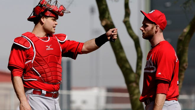 Reds catcher Devin Mesoraco talks with pitcher Tony Cingrani on Feb. 19 in Goodyear.