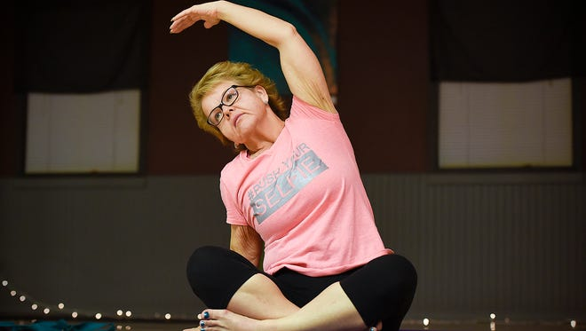 Tammy Habiger stretches during a yoga class Wednesday, Jan. 25, at Primal Body Massage & Movement in Waite Park. Habiger made the decision to go through with weight-loss surgery that changed her life.