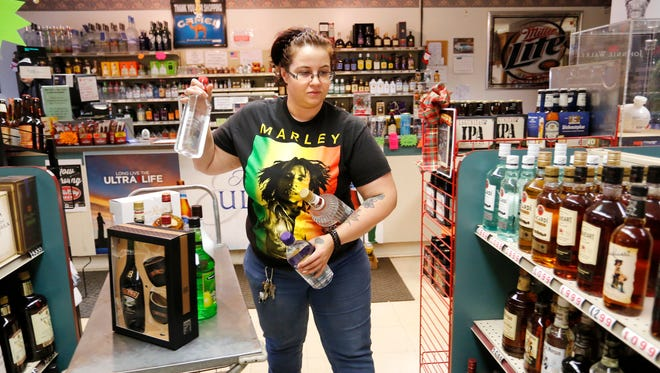 Store manager Tia McGee stocks the shelves at Tower Liquors Thursday, December 21, 2017, at 981 S. Creasy Lane in Lafayette.