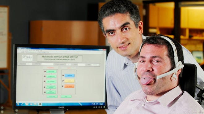 Maysam Ghovanloo, left, of Georgia Tech has developed new technology to allow users of motorized wheelchairs, including Jason DiSanto, to move the chair with their tongue.