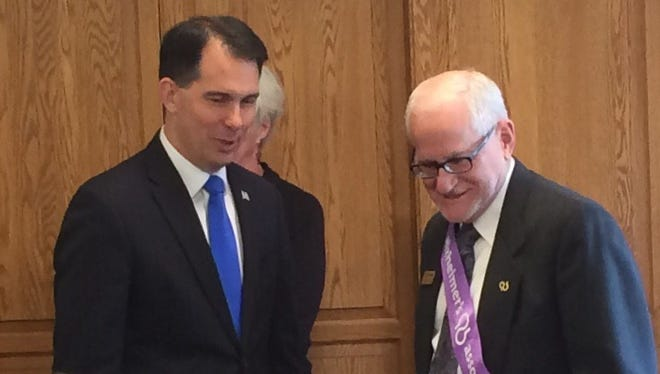 Wisconsin Gov. Scott Walker chats with a constituent before signing three dementia-related bills into law on Tuesday, March 22, 2016, in Green Bay.