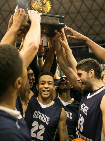 George Washington players hold a trophy after defeating