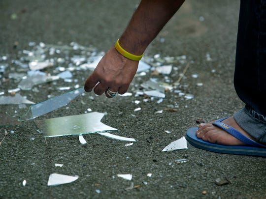 Shards of glass remain Friday after a crowd of young men broke windows Thursday at the Parkway home of Nepalese  refugees.