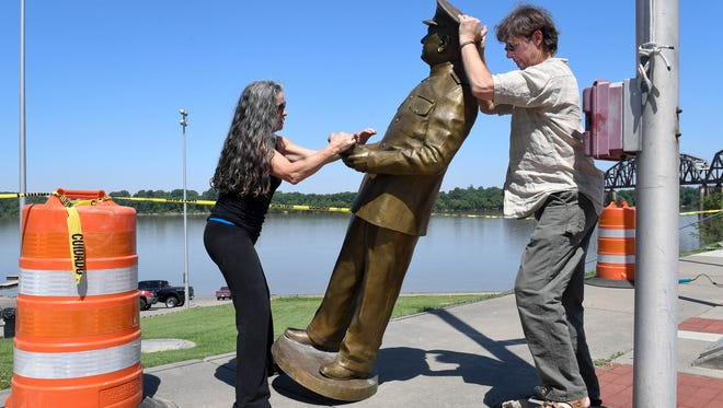 Dawn Yates (left) and Louisville based sculpture Raymond Graf maneuver the statue of World War II Admiral Husband E. Kimmel away from the base from which it has stood on the Henderson riverfront for a year and a half Wednesday. The statue will be missing for a week or two so that Graf can fix a couple of foundry errors that have been bugging him since it was installed in 2016, June 6, 2018.