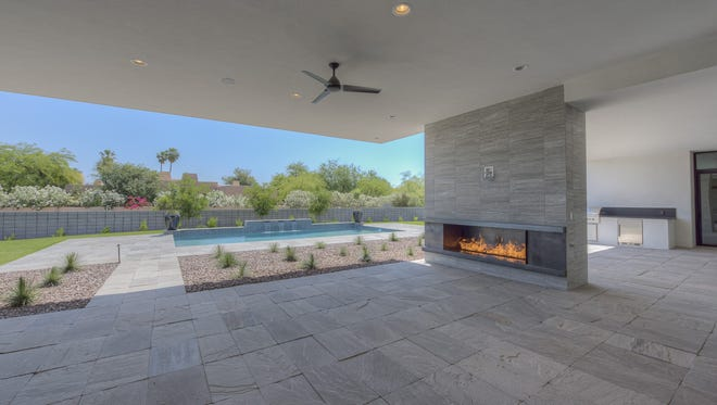 Phoenix Suns guard Devin Booker's new Paradise Valley home features four bedrooms, each with its own bathroom, a dining room with wine cellar, a chef's kitchen overlooking an outdoor living area with fireplace, retractable glass doors and a four-car garage.