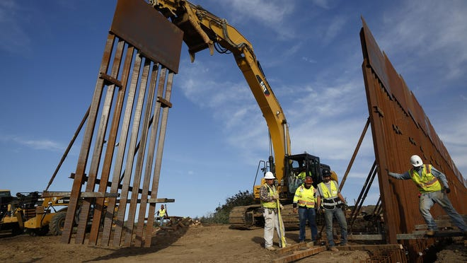 In this Jan. 9, 2019 file photo, construction crews install new border wall sections seen from Tijuana, Mexico.