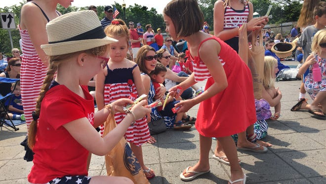 A group of young girls gather up candy tossed to them along the CarmelFest Fourth of July parade route on South Rangeline Road in Carmel on Saturday, July 4, 2015.
