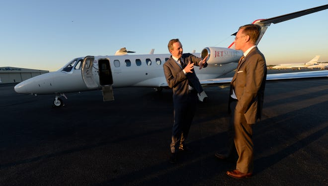 JetSuite CEO Alex Wilcox, left, and President and CFO Keith Rabin talk in front of one of their jets at Teterboro Airport in New Jersey.