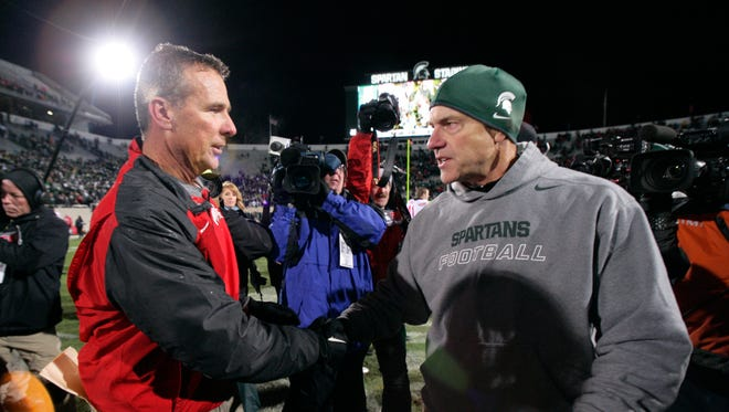 Ohio State coach Urban Meyer, left, and Michigan State coach Mark Dantonio shake hands following a game, Saturday, Nov. 8, 2014, in East Lansing, Mich.