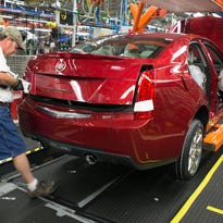 Workers build a 2013 Cadillac ATS at General Motors Co.'s Lansing Grand River assembly plant.