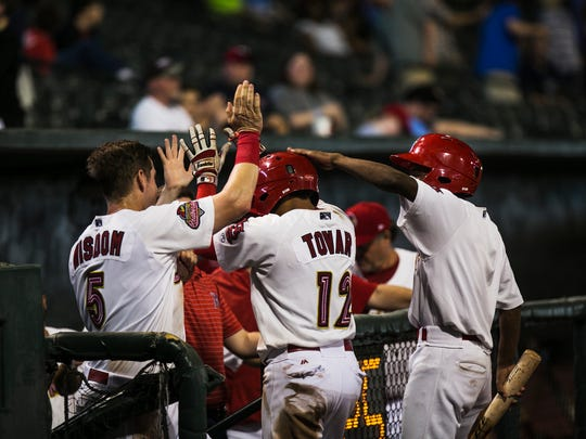 Memphis Redbirds infielder Wilfredo Tovar (12) is congratulated by teammate Patrick Wisdom (5) and bat boy Trey McCain after Tovar scored a run during a game against the Nashville Sounds on Aug. 17, 2017, at AutoZone Park. The Redbirds lost the game 11-8.