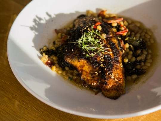 The blackened catfish is made with grilled blackened catfish, bacon, Fresno chiles, Anson Mills peas, braised collard greens, lemon juice and benne seeds at The Kitchen, located at Shelby Farms Park at 415 Great View East, Suite 101.