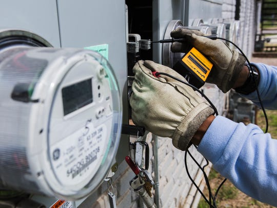 Maricco Rhodes, an electric meter technician for MLGW, installs a smart meter in South Memphis on May 2, 2018.