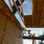 A framer with Fort Collins-based Gibbs Construction measures an area to cut while building a roof on a house at the Wildwing subdivision in Timnath.