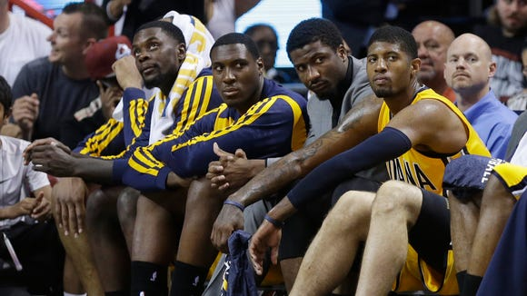 Indiana Pacers guard Lance Stephenson, left, center Ian Mahinmi, second from left, and forward Paul George, right, sit on the bench during the second half Game 6 in the NBA basketball playoffs Eastern Conference finals, Friday, May 30, 2014, in Miami. The Miami Heat defeated the  Pacers 117-92 to advance to the NBA Finals.