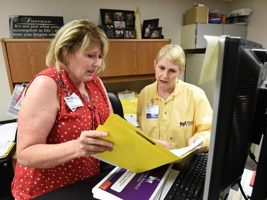 Becky Rose, director of volunteer services at Baxter Regional Medical Center, goes over a volunteer list with Jean Adams, one of nearly 600 volunteers who work at the hospital.