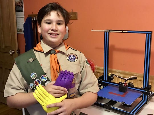 Princeton Academy eighth grader Chase Quijano of Hopewell in his Boy Scout troop 43 uniform holding two prosthetic limbs he built using a 3D printer.