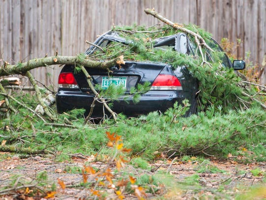 A car damaged by a falling tree is seen along Route 2A in Colchester on Monday, October 30, 2017.
