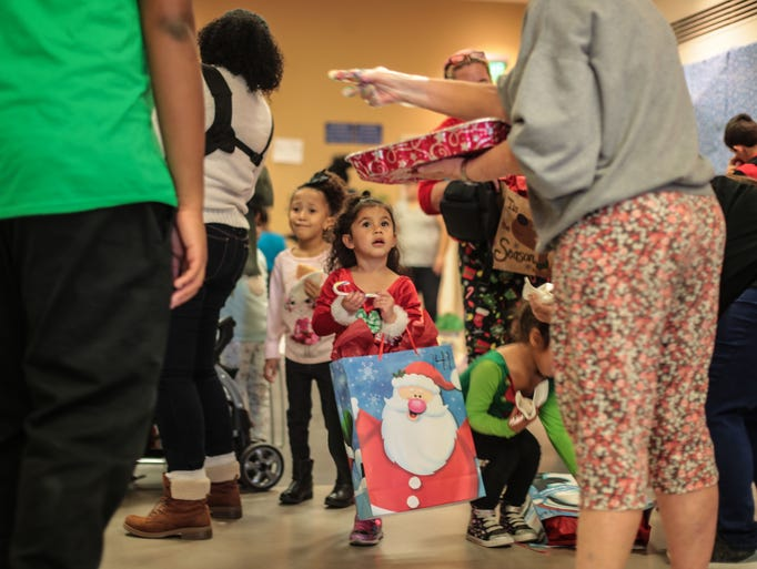 Sophie Salinas, 4, carries her toys at the John H.
