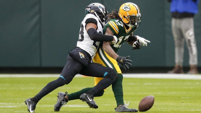 Jacksonville Jaguars' C.J. Henderson knocks the ball away from Green Bay Packers' Davante Adams after a catch during the second half of an NFL football game Sunday, Nov. 15, 2020, in Green Bay, Wis. The Jaguars recovered the fumble.