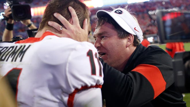 Georgia coach Kirby Smart celebrates with quarterback Jake Fromm (11) after the team's 24-17 win over Florida during an NCAA college football game Saturday, Nov. 2, 2019, in Jacksonville, Fla. (Joshua L. Jones/Athens Banner-Herald via AP)