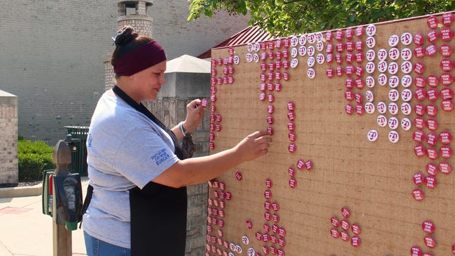 An employee at Frank's Restaurant picks out 'Heal the Zeel' buttons for herself and other staff to wear while they work. The Heal the Zeel button board, installed Friday, June 19 in downtown Zeeland, is a promotional campaign by the city of Zeeland.