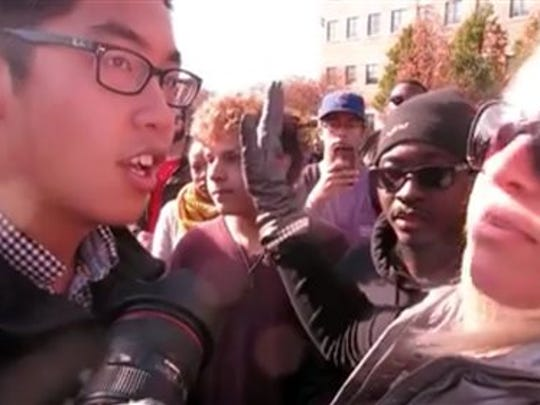 """In this Nov. 9, 2015 frame from video, Janna Basler, right, who works in the University of Missouri's office of Greek life, tells photographer Tim Tai, to """"leave these students alone"""" in their """"personal space,"""" in Columbia, Mo. Protesters credited with helping oust the University of Missouri System's president and the head of its flagship campus welcomed reporters to cover their demonstrations Tuesday, a day after a videotaped clash between some protesters and a student photographer drew media condemnation as an affront to the free press."""
