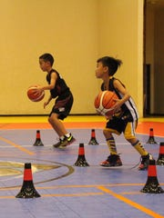 Youths practice ball-handling drills during a Guam Elite Basketball Academy camp.