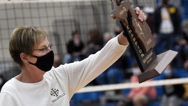 SMCC head coach Karen O'Brien holds up the Division 3 Regional championship trophy last week. New orders from the Michigan Department of Health and Human Services on Sunday night suspended all high school sports for at least three weeks.