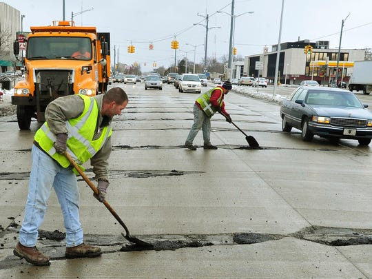 Greg Belanger and Jon Retaskie fill potholes on southbound Southfield, south of 9 mile in this February 28, 2013, file photo.