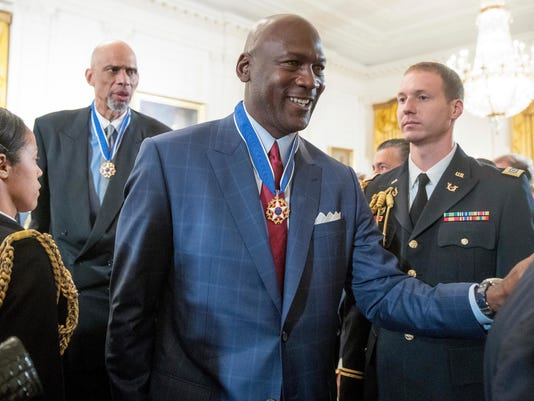 FILE - In this Nov. 22, 2016, file photo, former NBA basketball players Kareem Abdul Jabbar, left, and Michael Jordan, center, depart after receiving the Presidential Medal of Freedom at a ceremony in the East Room of the White House in Washington. Jordan voiced his support for freedom of speech and peaceful protest in a Sept. 24, 2017, statement to the Charlotte Observer following President Donald Trump's decision to rescind a White House invitation to the NBA champion Golden State Warriors. (AP Photo/Andrew Harnik, File)