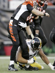 Quarterback Carson Palmer is hit in the knee by Kimo