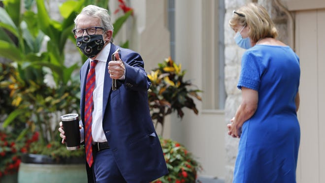 Ohio Governor Mike DeWine, left, and his wife Fran, walk into their residence Thursday after he was prevented from greeting the president in Cleveland by a positive coroanvirus test. He's now been determined three times to be negative for the virus.