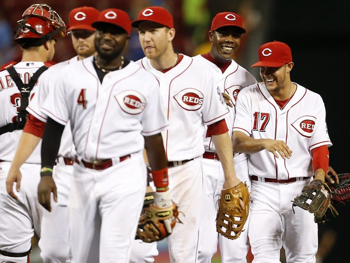 Cincinnati Reds relief pitcher Aroldis Chapman (54) reacts with third baseman Kris Negron (17) after a deep fly ball to center field by the Chicago Cubs second baseman Javier Baez (9) for the third out ending the game in the ninth inning at Great American Ball Park.
