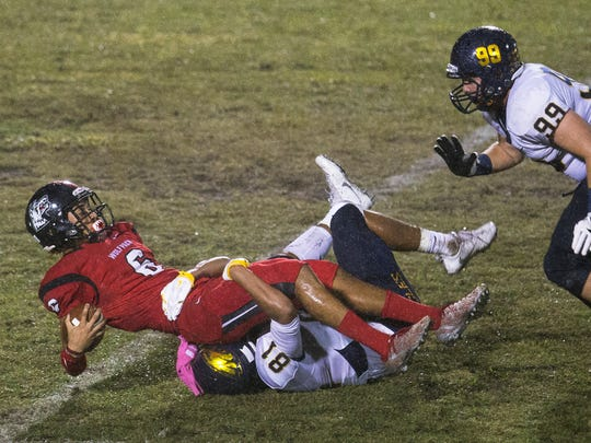 Naples High School defenders bring down South Fort Myers' Jeshaun Jones during second quarter play Friday at South Fort Myers High School. Naples beat South 39-12.