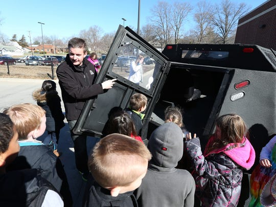 Zach Sharpe, a weather chaser from Norwalk, shows students at Stowe Elementary School in Des Moines the inside of Dorothy, a 5-ton vehicle members of the Iowa Storm Chasing Network use when they encounter tornados.