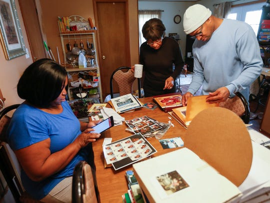 From left, Ann Lewis, Jeannie Harper and Tyrone Lewis look through photographs of James Lewis on Monday, January 2, 2017. James Lewis was shot and killed by Springfield police early January 1, 2017 after police say he refused to drop his gun. The Lewis family says that James suffered from mental illness.