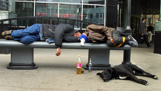 In this September 2005 file photo, men sleep after drinking on a bench in downtown Moscow. Russian men who down large amounts of vodka -- and too many do -- have an extraordinarily high risk of an early death, a new study says.