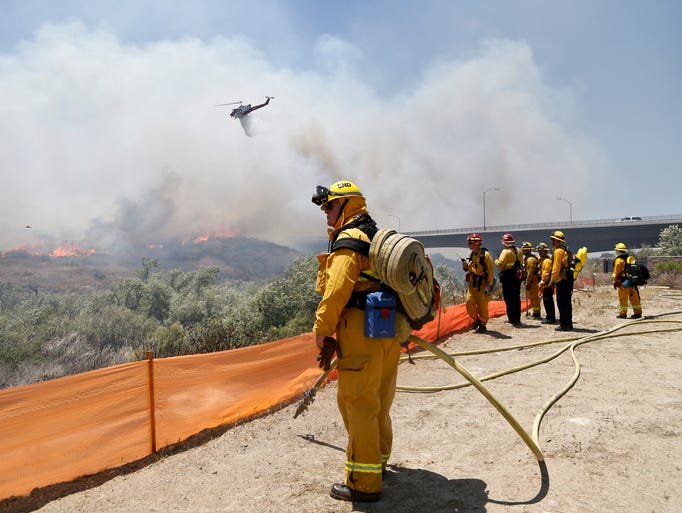 Firefighters watch from a ridge as a helicopter drops retardant on a out-of- control wild fire Tuesday, May 13, 2014, in San Diego.